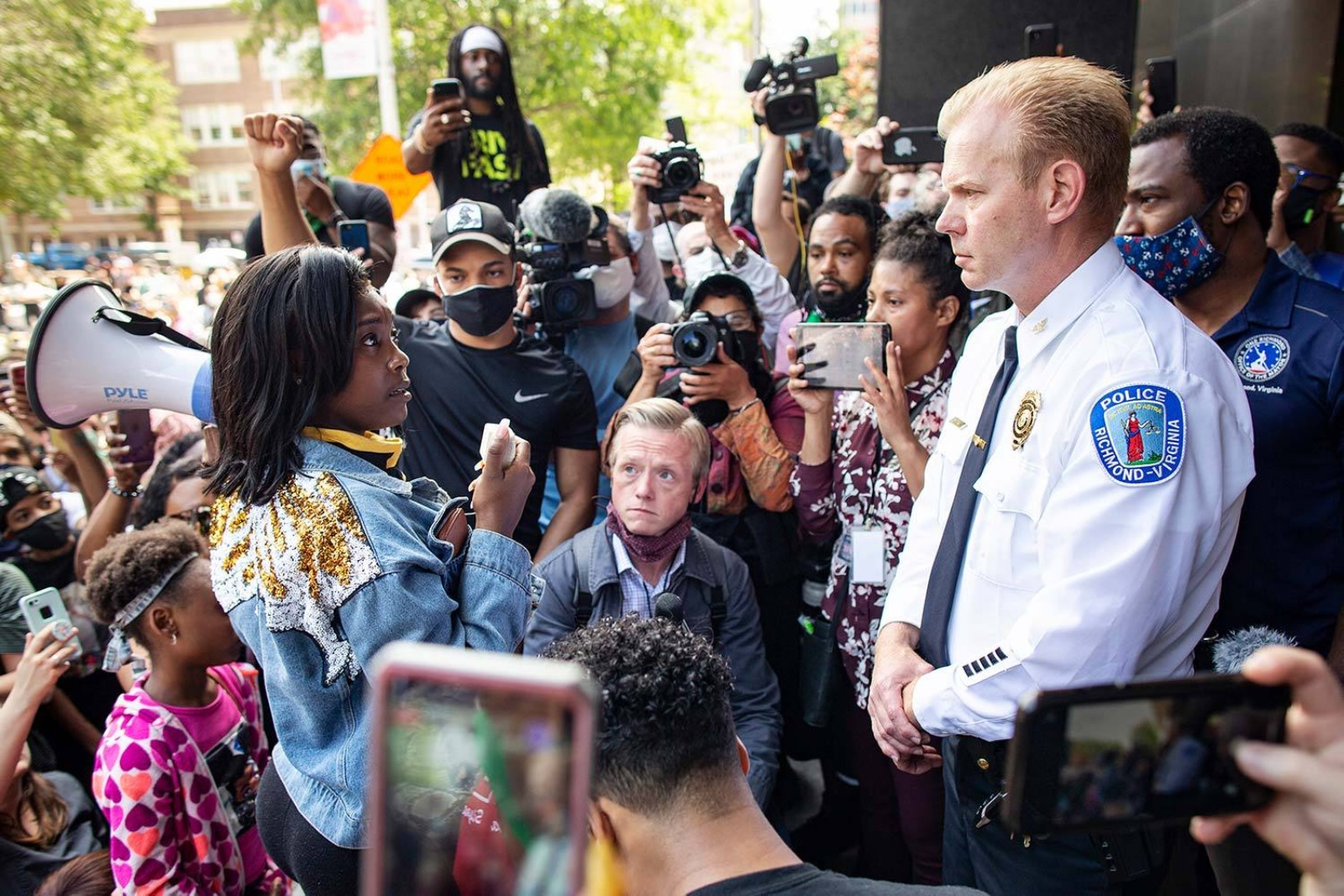 Brian Palmer photograph of female protestor looking at police chief in crowd of protestors